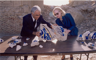 Ambassador Kennedy and Minister of Culture Aydogdiyev standing at table examining blue and white mosaic pieces