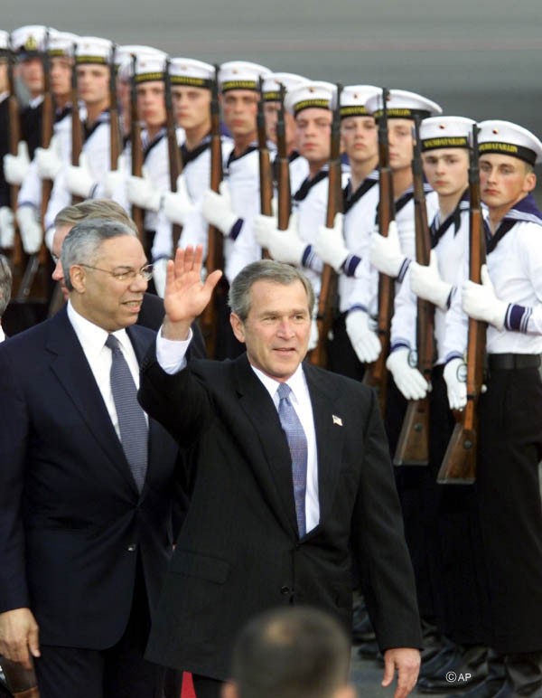 President Bush waves as he and Secretary Powell walk past honor guards in dress uniforms