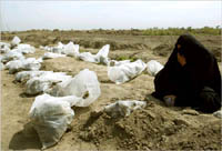 An Iraqi women mourns next to remians of bodies exhumed from a mass grave. AP photo.
