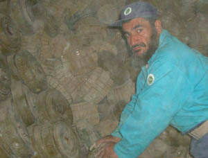A deminer from the Demining Agency for Afghanistan begins removing anti-tank mines haphazardly piled in one of many unsecured bunkers in this ammunition supply point in Kandahar Province. Photo by Robert Gannon, RONCO Consulting Corporation, June 2003.