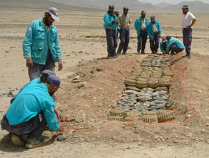 Demining Agency for Afghanistan personnel prepare one of several batches of anti-tank mines taken from an unsecured ammunition supply point in Kandahar Province for destruction, ensuring that the mines or their explosive contents will never be used by terrorists. Photo by Robert Gannon, RONCO Consulting Corporation, June 2003.