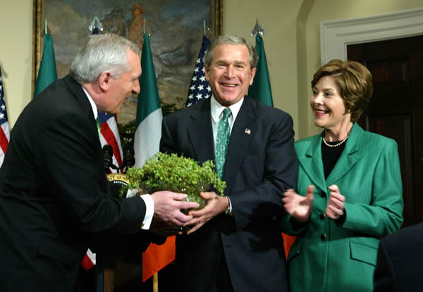 President Bush, center, and first lady Laura Bush, right, receive a bowl of shamrocks from Irish Prime Minister Bertie Ahern during a ceremony marking St. Patricks Day at the White House. [AP photo]