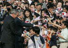 President Bush and Japan's Prime Minister Junichiro Koizumi shake hands with children.