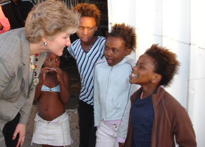Under Secretary Karen Hughes jokes with young children of the Masiphumelele Township outside of Cape Town, South Africa [State Department Photo 4/06].