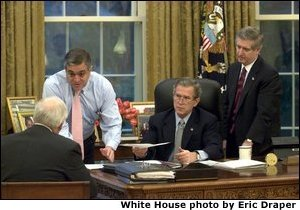 President George W. Bush receives an update on the status of military action in Iraq Thursday morning, March 20, 2003, in the Oval Office. Present are Vice President Dick Cheney, CIA Director George T