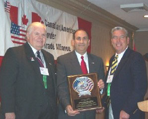 Assistant Secretary Noriega receives a plaque of appreciation from Canadian/American Border Trade Alliance President Jim Phillips[left]. At right is Can/Am BTA Executive Board Member Mike Dahm.