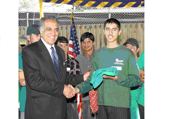 July 22, 2004, Kabul, Afghanistan: Mir Hamidullah, a Seeds of Peace Youth Leader, gives a Seeds of Peace t-shirt to U.S. Ambassador and Special Presidential Envoy Zalmay Khalilzad.