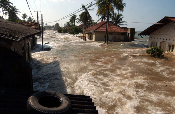 Tidal waves wash through houses at Maddampegama, about 38 miles south of Colombo, Sri Lanka, Sunday, Dec. 26, 2004. Massive waves triggered by earthquakes crashed into villages along a wide stretch of Sri Lankan coast on Sunday, killing more than 2,100 people and displacing a million others. AP/Wide World Photo