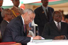 Secretary Powell signs the Sudan Peace agreement as a witness, as Vice President of Sudan Ali Osman Taha, left, and President of Kenya Mwai Kibaki, right, wait, at Nyayo Stadium Nairobi, Kenya, Sunday, January 9.