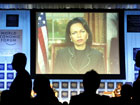Secretary Rice speaks on screen by video link, during a plenary session entitled: The Guiding Principles and Values for U.S. Politicies at the World Economic Forum in Davos, Switzerland, Jan. 26, 2006 [� AP/WWP]