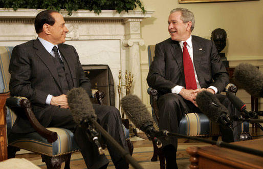President George W. Bush smiles as he and Italian Prime Minister Silvio Berlusconi meet the media in the Oval Office Tuesday, Feb. 28, 2006. [White House photo]