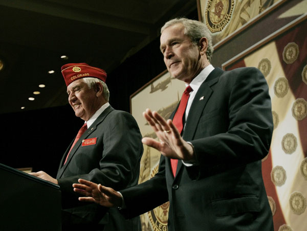 President Bush gestures for people to take their seats as he is introduced by Thomas L. Bock, National Commander of the American Legion, before speaking on the war against terrorism before an American