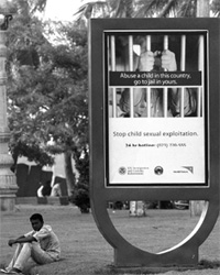 Sign reads: Abuse a child in this country, go to jail in yours. Stop child sexual exploitation. 24 hr hotline: 023-720-555, U.S. Immigration and Customs Enforcement, WorldVision. [AP/WWP photo]