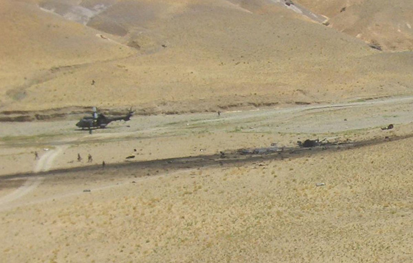 In this photo released by the Spanish Defense Ministry a Spanish army helicopter, left, sits on the ground after making an emergency landing beside wreckage, dark area at center of picture, from another Spanish army helicopter that crashed killing 17 Spanish soldiers in western Afghanistan, Tuesday Aug. 16, 2005. The Spanish Defense Minister Jose Bono says that he does not rule out hostile fire as the possible cause of the deadly crash. [AP Photo/Spanish Defense Ministry]
