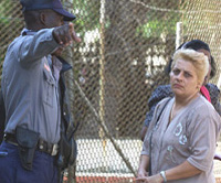 Cuban police officer stops a woman from entering the U.S. Interests Section in Havana. AP Photo.