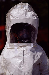 A health worker stands in a protective hazardous materials suit.
