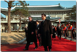 "President George W. Bush and President Kim Dae-Jung proceed through an arrival ceremony at The Blue House in Seoul, Republic of Korea, Feb. 20. ""I understand how important this relationship is to our country, and the United States is strongly committed to the security of South Korea. We'll honor our commitments. Make no mistake about it that we stand firm behind peace in the Peninsula."" White House photo by Paul Morse"