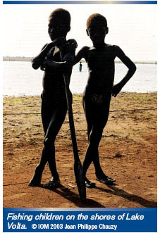 Two boys, victims of trafficking in persons, stand on the shore of Lake Volta, Ghana, ready to board a boat to fish. IOM photo.