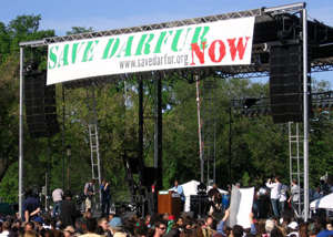 Assistant Frazer speaking under Save Darfur banner before large crown on the Mall [State Department Photo April 2006]
