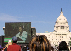 Assistant Secretary Frazer appears on large screen during the Save Darfur rally with the Capitol Dome in the background. [State Department Photo April 2006]