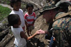 A U.S. Marine Gunnery Sergeant speaks with children from the village of Guinsaugon in Leyte.  Members of the U.S. 31st Marine Expeditionary Unit, based in Okinawa, Japan, came to Leyte on the USS Harpers Ferry and the USS Essex in order to bring humanitarian relief supplies to landslide victims.  The U.S. Government is also supplying emergency funds and supplies such as blankets, water, and body bags through the U.S. Agency for International Development.