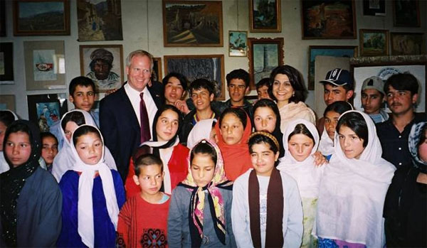 Council Member Tim McBride and Shamim Jawad in Kabul, Afghanistan surrounded by school children, March 2005. [State Department photo]