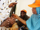A World Health Organization ,WHO, official gives a dose of Polio Vaccine to Somali child in Mogadishu, Somalia. [AP PhotoSept. 2006]