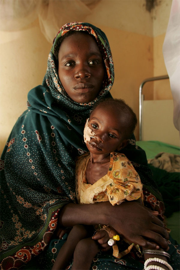 A mother holds her child who gets treatment in the hospital of El Fasher in western Sudan. AP/Wide World Photo.