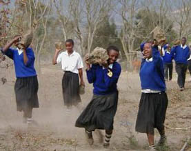 Students carrying stones to building site of 36-bed girls' hostel being constructed in Tanzania