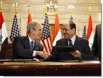 Date: 12/14/2008 Location: Baghdad, Iraq Description: President George W. Bush and Iraqi Prime Minister Nuri al-Maliki shake hands following the signing of the Strategic Framework Agreement and Security Agreement at a joint news conference Sunday, Dec. 14, 2008, at the Prime Minister